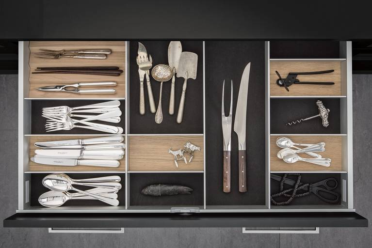 Cutlery inserts in light oak on dark grey flocked mats in SieMatic kitchen drawer