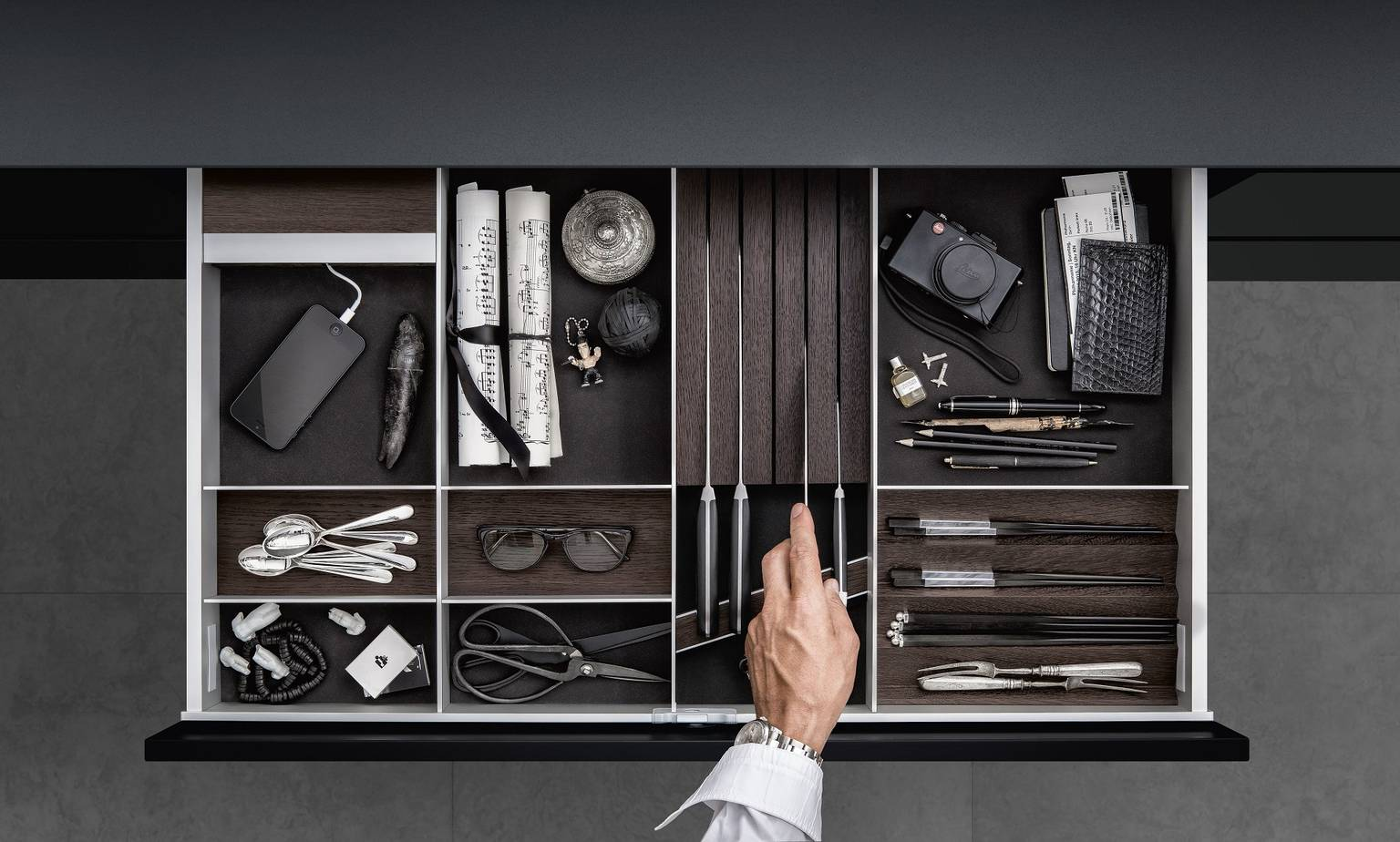 SieMatic aluminum kitchen interior accessories in dark smoked chestnut provide a place for iPhone, cutlery and knives.