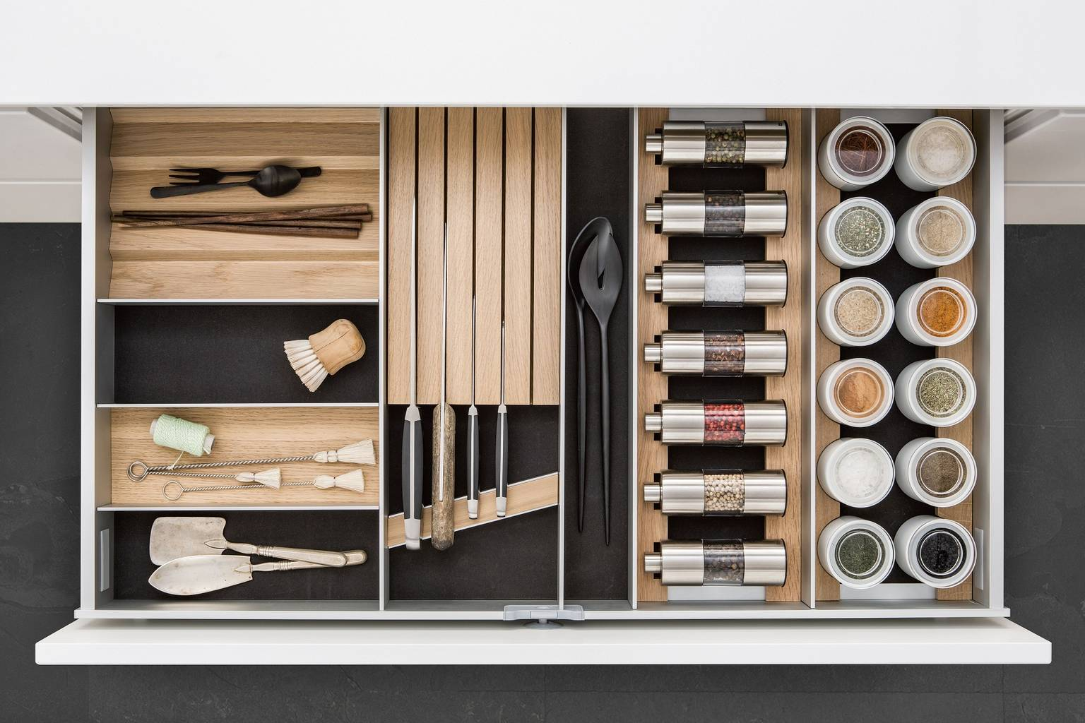 SieMatic aluminum kitchen interior accessories in light oak offer space for spice mills, porcelain jars and knives.