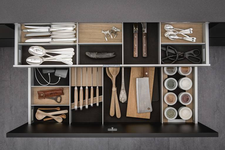Cutlery inserts, porcelain jars, knife block and USB charging station for iPhones inside SieMatic drawers